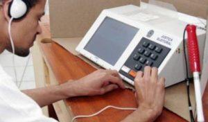 Homem com deficiência visual de camisa branca, com fone de ouvido, simula votação em urna eletrônica apoiada em uma mesa de madeira. Há uma bengala apoiada na mesa, ao lado da urna.