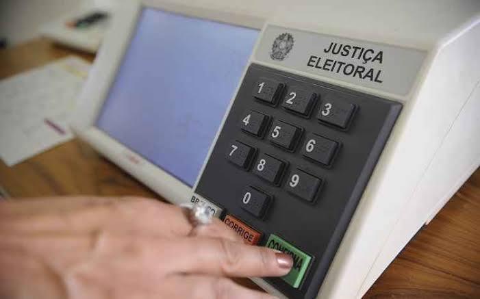 """Mão de mulher aperta a tecla """"confirma"""" da urna eletrônica"""