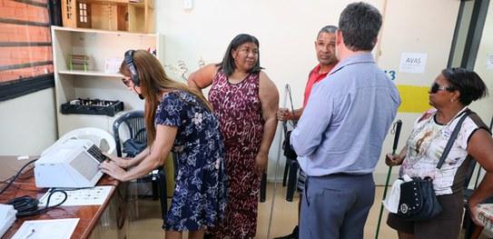 Mulher de vestido azul com fone de ouvido simula votação em urna eletrônica. Outras pessoas estão na fila para fazer a simulação. Todos são pessoas com deficiência visual