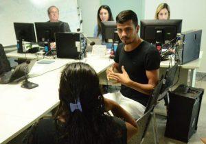 Servidores trabalham no computador enquanto um rapaz faz interpretação de libras para uma jovem, que está de costas